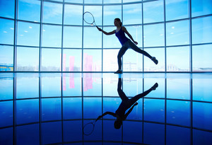 Young female playing tennis in gym on background of window