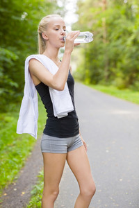 Young female runner drinking water after workout