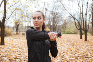 Young female runner in warm clothes and headphones looking aside in autumn park while make sport exercise