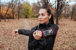 Young female runner in warm clothes and headphones looking aside in autumn park