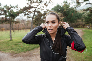 Young female runner in warm clothes with hood and headphones looking aside in autumn park