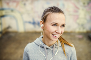 Young female runner is having break and listening to music in the street