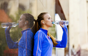 Young female runner is having break, drinking water and listening to music during the run in city center