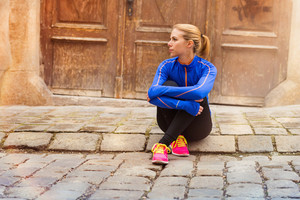 Young female runner sitting on tiled pavement in old city center