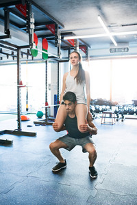 Young fit couple in modern crossfit gym exercising. Man carrying woman on his shoulders, doing squats.