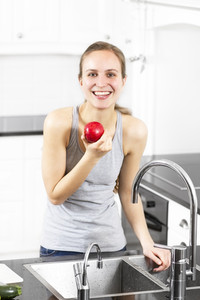 Young fit / healthy / sporty woman wash / eat an apple. Modern and exclusive kitchen.