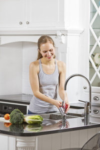 Young fit / healthy / sporty woman wash / prepare vegetables and fruit.