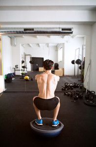 Young fit hispanic man exercising, doing squats on fitness ball in crossfit gym. Rear view.