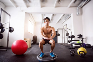 Young fit hispanic man exercising, doing squats on fitness ball in crossfit gym.
