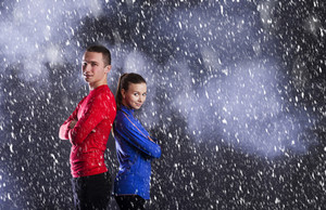 Young fitness athletes are posing in studio with black dusty background.