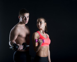 Young fitness models are posing in studio