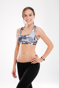 Young fitness woman in studio. looking at camera. isolated white background. arm at hip