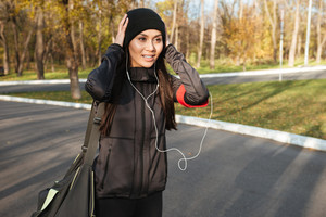 Young fitness woman in warm clothes and earphones in autumn park holding bag. Look aside.