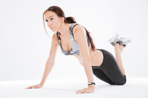 Young fitness woman on the floor in studio. isolated white background