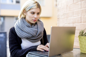 Young Focused Woman Working On Laptop At Outdoor Cafe