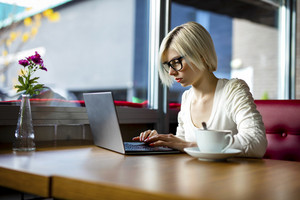 Young Focused Woman Working On Laptop In Cafe