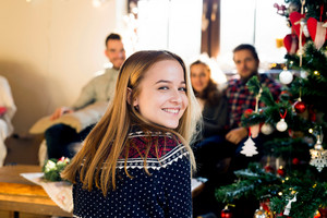 Young friends at decorated Christmas tree celebrating Christmas together. Teenage girl in sweater with nordic pattern smiling.