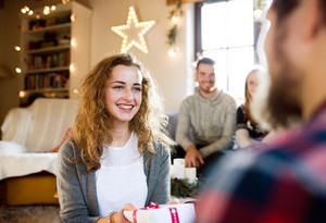 Young friends in decorated living room celebrating Christmas together exchanging gifts. Hipster man giving gift to beautiful young woman.