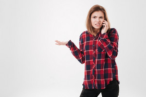 Young frustrated girl in plaid shirt talking on mobile phone and looking at camera isolated on a white background