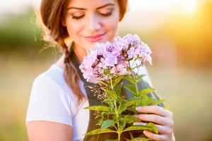 Young gardener in her garden holding flowers, green sunny nature at sunset