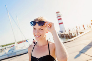 Young girl in a bikini posing near the shoreline, lighthouse in the background, sunny summer
