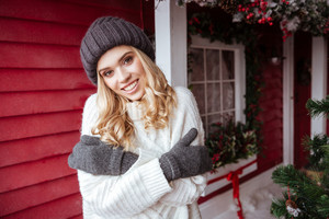 Young girl in sweater, hat and mittens near the house. looking at camera