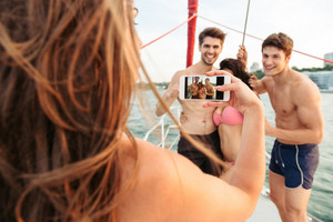 Young girl making picture of her friends having fun on the yacht