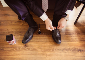 Young groom putting on shoes and getting ready for wedding.