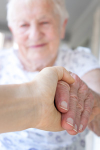 Young hand holding senior lady's hand on porch