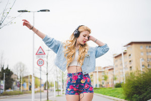 Young handosme caucasian blonde girl listening music walking in the suburbs - technology, freedom, emancipation concept