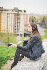 Young handosme eastern brunette girl listening music in a park in the city - technology, freedom, emancipation concept