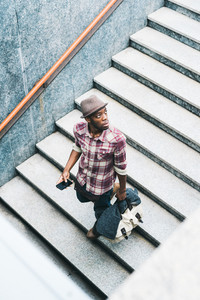 Young handsome afro black man descending the underground staircase, looking upward, holding a bag and a smartphone - technology, travel concept