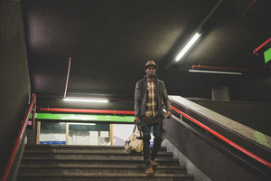 Young handsome afro black man going downstairs in the underground, holding a bag, overlooking left - youth, transport concept