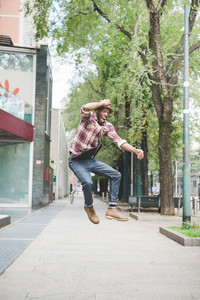 Young handsome afro black man jumping in the street of the city, looking upward smiling, holding his hat on his head - surprised, jumping, having fun concept