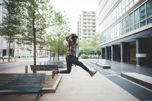 Young handsome afro black man jumping in the street of the city, looking upward surprised, holding his hat on his head - surprised, jumping, having fun concept