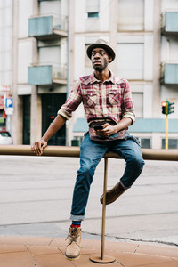 young handsome afro black man sitting on a handrail outside in the city, overlooking right, smartphone handheld, pensive - serious, thoughtful, thinking future concept
