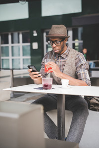 young handsome afro black man sitting on a table, smartphone handhold, looking down the screen, drinking a juice - technology, social network, communication concept