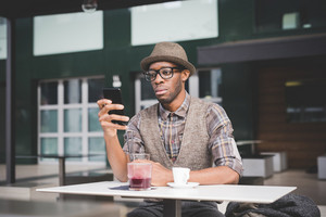 young handsome afro black man sitting on a table, smartphone handhold, looking down the screen - technology, social network, communication concept