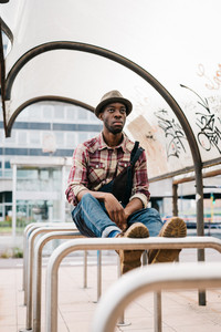 young handsome afro black man sitting outside in the city, wearing jeans overalls and checked shirt, overlooking, pensive - thoughtful, thinking future, serious concept