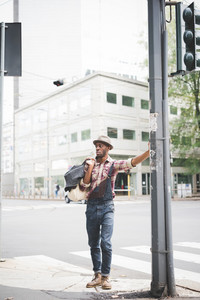 young handsome afro black man standing outside in the city leaning against a pole, holding a bag, overlooking right, pensive - serious, thoughtful concept - wearing jeans overalls and checked shirt