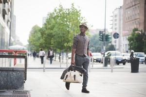 Young handsome afro black man walking in the street of the city, holding a bag, overlooking right with glasses, pensive , hands in pocket- thoughtful, serious concept