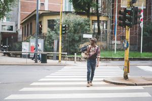young handsome afro black man walking on pedestrian crossing, looking right, holding a bag,wearing jeans overalls and checked shirt