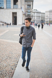 young handsome alternative dark model man in town listening to music with headphones and smartphone connected wireless