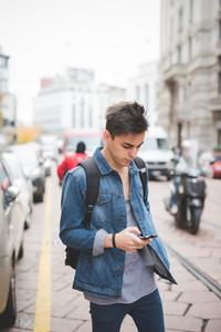 young handsome alternative dark model man in town using smartphone
