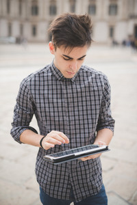 young handsome alternative dark model man in town using tablet technological device connected wireless