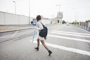 young handsome asiatic chinese woman crossing the street of the city, holding a blue umbrella and a backpack