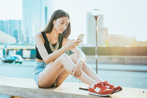 Young handsome asiatic long brown straight hair woman listening music with smartphone while using a smartphone, looking downward the screen - technology, music, relaxing concept