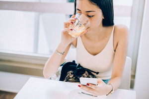 Young handsome asiatic long brown straight hair woman sitting in a bar, drinking a juice and using a smart phone, looking downward the screen - technology, social network, relaxing concept