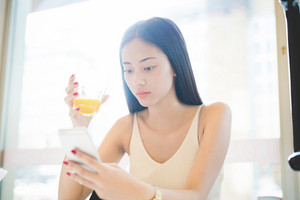 Young handsome asiatic long brown straight hair woman sitting  in a bar, drinking a juice and using a smartphone, looking downward the screen - technology, social network, relaxing concept