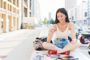 Young handsome asiatic long brown straight hair woman sitting on a small wall, cross-legged, listening music with earphones, looking downward the screen, smiling - technology, happiness concept